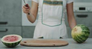 专业厨师妇女在照相机画象夺取前面的厨房里切了与一把大刀子的一个大西瓜 影视素材