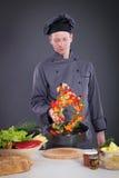 专业厨师投掷在平底锅的食物 免版税库存照片