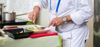 专业厨师,打扮在白色和准备一顿平衡的健康膳食 免版税库存图片