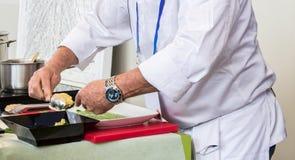 专业厨师,打扮在白色,准备一顿可口精妙的膳食 免版税库存图片