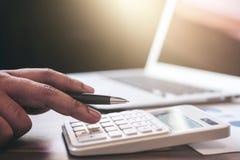 专业商人与计算器一起使用,做财务 免版税库存图片