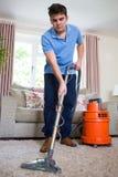 专业地清洗地毯的年轻人 免版税库存图片