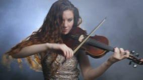 专业地演奏在小提琴的美丽的女孩交响乐在音乐学院  股票录像