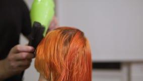 专业头发梳妆台特写镜头视图使用一hairdryer的在理发以后 美容院的年轻红头发人妇女 影视素材