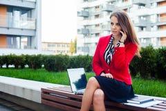 年轻专业女商人坐室外与计算机 库存图片