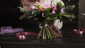 专业女孩卖花人束缚花束的底部与丝绸桃红色丝带的 黑暗的演播室 慢的行动 股票视频