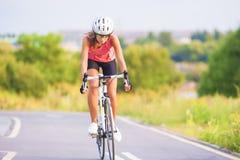 专业女性炫耀自行车的运动员 库存图片
