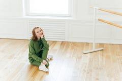 专业女性舞蹈家照片在地板上有休息在训练以后,摆在芭蕾纬向条花附近,有芭蕾类,佩带绿色 免版税库存图片