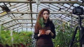 专业女性花匠记录关于从事园艺的讲解与站立里面宽敞温室的照相机和 影视素材