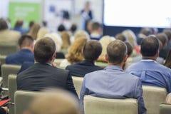 专业女性主人讲话在大量观众前面在业务会议期间 免版税库存图片