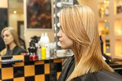 专业她的沙龙的客户的美发师洗染的头发 在做法以后的颜色头发 妇女展示头发 免版税库存照片