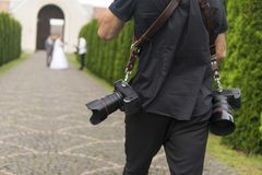 专业婚礼摄影师在庭院里为新娘和新郎,行动的摄影师照相与两 库存图片