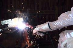 专业工业焊工的手有火炬和防护手套焊接金属钢的与火花在工厂 库存图片