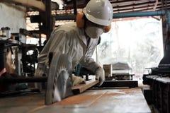 专业年轻工人软的焦点白色制服和切开一块木头在桌上的安全设备的看见了在鲤鱼的机器 免版税库存图片