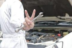 专业年轻技工的手供以人员拿着板钳,并且举它的两个手指是展示作战与工作与在开放的汽车 免版税库存图片