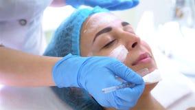 专业应用面膜的美容师和皮肤病学家在妇女面孔在发廊 拉紧和rej的方法 股票视频
