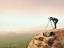 专业摄影师为与镜子照相机和三脚架的有薄雾的风景照相 免版税库存照片