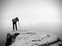 专业摄影师为与镜子照相机和三脚架的有薄雾的风景照相 图库摄影