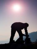 专业摄影师包装照相机入在岩石峰顶的背包  梦想的老保守风景,反弹橙色桃红色有薄雾的日出 免版税图库摄影