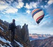 专业摄影师拍与大照相机的照片在岩石峰顶  免版税库存图片