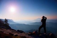 专业摄影师拍与镜子照相机的照片在岩石峰顶  梦想的老保守风景,反弹橙色桃红色有薄雾的日出 免版税库存图片