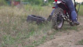 专业摩托车骑士漂泊和起动在地面上的一辆摩托车,骑自行车的人做在摩托车的一个把戏 慢的行动 股票录像