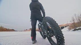 专业极端运动员骑自行车的人站立在室外的一辆肥胖自行车 骑自行车者在冬天雪森林人步行斜倚 影视素材