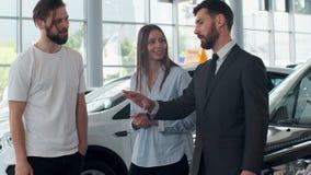 专业汽车推销员告诉感兴趣的买家关于豪华汽车的美好的夫妇在汽车展示会一会儿人和 影视素材