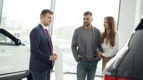 专业汽车推销员告诉感兴趣的买家关于豪华汽车的美好的夫妇在汽车展示会,当人和时 影视素材