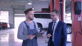 专业汽车维护,有剪贴板的技工与客户联络在机械推力的汽车附近 股票录像
