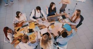 专业混合的族种年轻商业公司工作者谈论创新在现代办公室,配合精神顶视图 影视素材