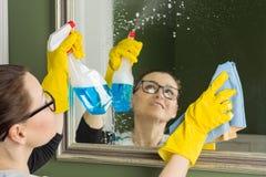 专业清洁服务 做清洁的橡胶手套的女工在卫生间,清洗镜子与旧布和洗涤剂 库存图片