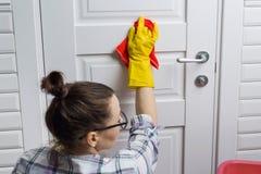 专业清洁服务 橡胶手套的女工在卫生间、清洗的门与旧布和洗涤剂里的做清洁 库存图片