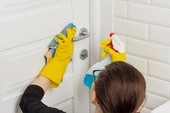 专业清洁服务 橡胶手套的女工在卫生间、清洗的门与旧布和洗涤剂里的做清洁 免版税库存图片