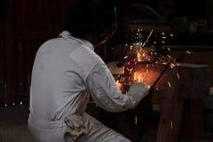 专业焊工人和与火花的防护盔甲焊接钢侧视图有火炬的在工厂 行业概念 免版税图库摄影