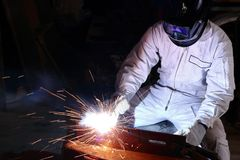 专业焊工人焊接钢正面图与火花的在工厂有拷贝空间背景 行业概念 免版税库存图片