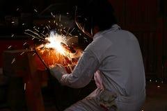 专业焊工和与火花的防护盔甲焊接钢后面看法有火炬的在工厂 行业概念 库存照片