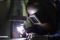 专业焊工焊接金属零件 免版税库存图片