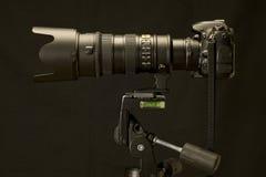 专业照相机和变焦镜头在修改过的三脚架 库存图片