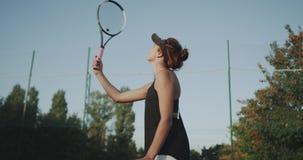 专业球员妇女,敲打与然后拿着球的球拍的网球使用手,微笑的面孔 股票录像
