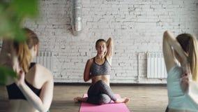 专业瑜伽老师展示在母牛面孔姿势的胳膊锁并且解释技术 学生尝试和 影视素材
