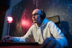 专业男孩游戏玩家充当在eSports比赛的电子游戏或网吧 他佩带耳机并且讲话 库存照片