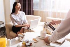 专业男性在杯子的侍者倾吐的咖啡 免版税库存图片