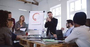 专业精力充沛的中部变老了企业分享经验的辅导者人与不同种族的队在现代时髦办公室 股票录像