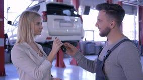 专业维护,有握手的钥匙的汽车机械师对女性客户然后看与微笑的照相机  股票录像