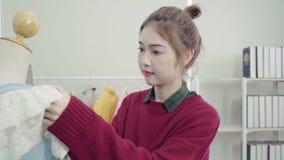 专业美丽的亚裔女性在一个时装模特衣物设计的时尚编辑运转的测量的礼服在演播室 影视素材