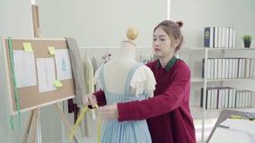 专业美丽的亚裔女性在一个时装模特衣物设计的时尚编辑运转的测量的礼服在演播室 股票录像