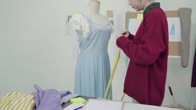 专业美丽的亚裔女性在一个时装模特衣物设计的时尚编辑运转的测量的礼服在演播室 股票视频