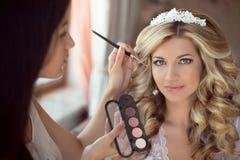 专业美发师在婚礼之日做构成新娘 豆杆 免版税图库摄影