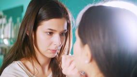 专业美发师女性做补偿在镜子前面的少妇在美容院 影视素材
